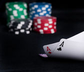 Two aces high on black table with chips — Stock Photo