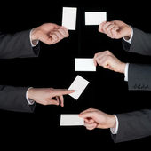 Hands hold business cards collage on black — Stock Photo