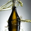 Stock Photo: Full champagne bottle with splashes