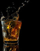 Glass of whiskey with splash, isolated on black — Stock Photo