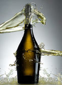 Full champagne bottle with splashes — Stock Photo