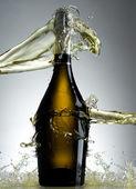 Full champagne bottle with splashes — Stock Photo