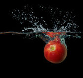 Ripe tomato falls under water with a big splash on black — Stock Photo