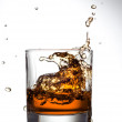 Whisky splashing out of glass on a white — Stock Photo