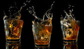 Glass of whiskey with splash — Stock Photo