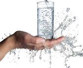 Mains humaines avec le verre et l'eau éclaboussant sur eux — Photo