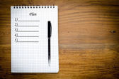 Black notebook with pen on a wood background — Stock Photo