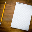 Black notebook with pencile on a wood background — Stock Photo