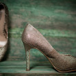 Golden women shoes on wooden background — Stock Photo
