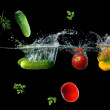 Fresh vegetables splashing in water on black — Stock Photo