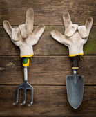 Gardening tools in working gloves on wooden — Stock Photo