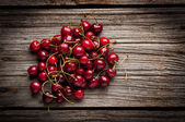 Cherries on wooden table with water drops — Stock Photo