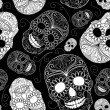 Seamless black and white background with skulls — Stock Vector