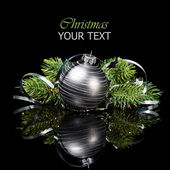 Christmas ornament with pine tree branches on a black background — Stock Photo