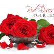 Red roses and petals in a wooden spa bowl - Stock Photo