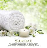 Frontera spa con toalla enrollada, flores, velas y bokeh natural — Foto de Stock
