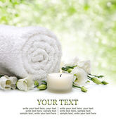 Spa border with rolled towel, flowers, candlelight and natural bokeh — Stock Photo