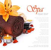 Wellness massage grens met handdoek en oranje lily bloem — Stockfoto