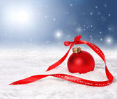 Christmas background with red bauble and merry christmas ribbon — Stock Photo