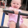A baby is smiling in a swing — Stock Photo