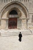 Padre cristão andando para a igreja antiga — Fotografia Stock