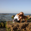 Blonde girl with dog on the sea  — Stock Photo
