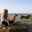 Stock Photo: Small girl with her dog on berth near sea
