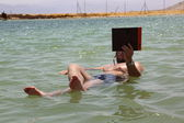 Man floating in a dead sea with a book — Stock Photo