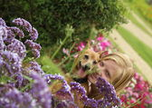 Beautiful girl and dog at the flowers — Stock Photo