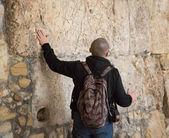 Tourist touches the ancient walls of Jerusalem — Stock Photo