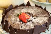 Round chocolate cake with pieces of dark chocolate and fresh strawberries — Photo