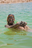 Young woman taking mud treatment at the Dead Sea — Stock Photo