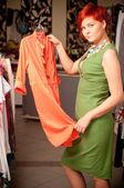 Young woman choosing dress — Stock Photo