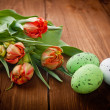 Birds eggs in nest with tulip flowers on vintage wooden backgrou — Stock Photo