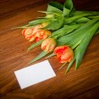 Royalty-Free Stock Photo: Tulips and blank card on old wooden boards