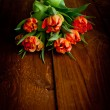 Tulips on rustic wooden table — Stock Photo