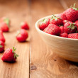 Strawberries in a Bowl, ona a wooden background — Stock Photo