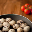 Frying pan with raw quail eggs on wooden boards — Stockfoto