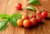 Fresh, ripe cherry tomatoes on an old chopping board. Basil leav — Stock Photo