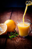 Orange and orange juice on a wooden background — Stock Photo