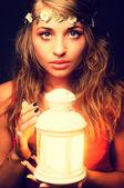 Beautiful girl with lantern seeking in night. Vintage retouching — Stock Photo