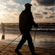 Man cultivating Nordic Walking on the beach — Stok fotoğraf