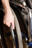 Close-up of male hand on wheel of wheelchair — Stock Photo