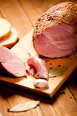 Whole ham with bread in the background, selective focus — Foto de Stock