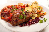 Fillet of duck with roasted potatoes, vegetables and cranberry — Stock Photo