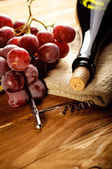 Red wine and grapes in vintage setting — Stock Photo