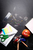 School supplies on the background of blackboard — Stock Photo