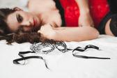 молодая женщина, лежа на кровати, глядя на маски — Стоковое фото