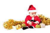 Serious baby dress as santa looking at baubles — Stock Photo