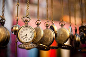 Pocketwatches hanging over multicolor background — Stock Photo